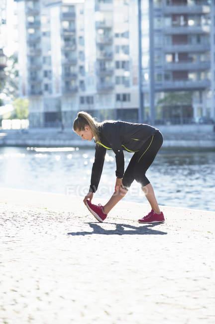 Женщина в спортивной одежде тренируется вдоль набережной — стоковое фото