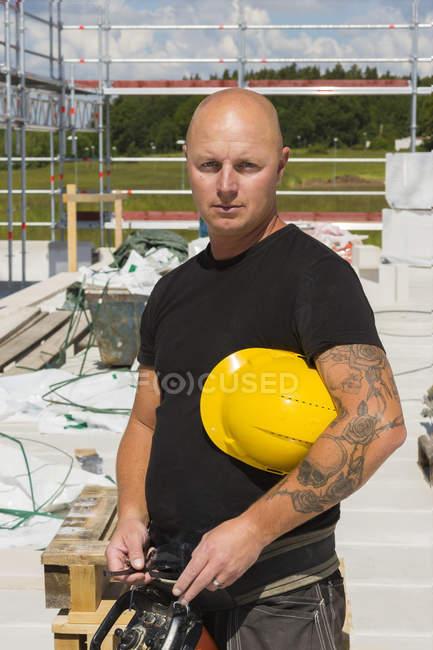 Працівник на будівельному майданчику дивиться на камеру, зосереджується на вибірці. — стокове фото