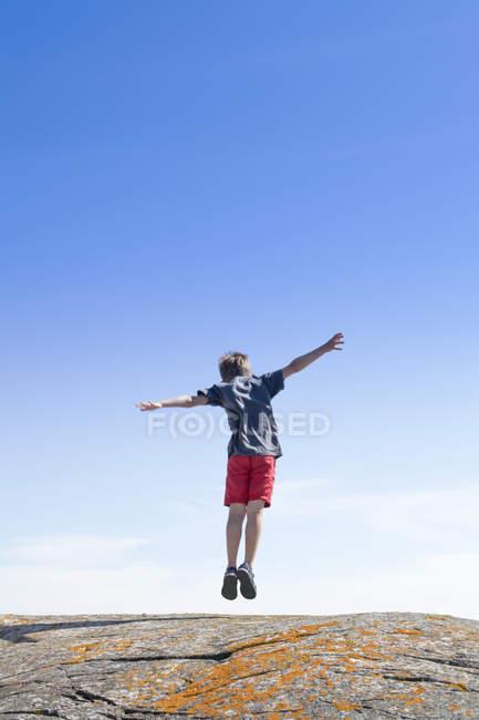 Vue arrière du garçon sautant sur la roche contre le ciel bleu — Photo de stock