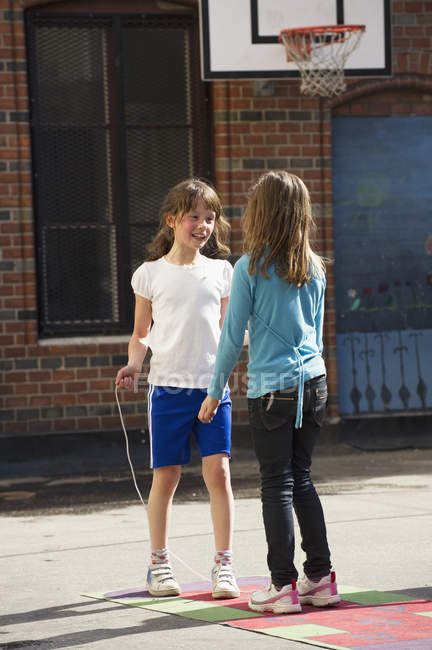 Two girls playing in schoolyard, selective focus — Stock Photo