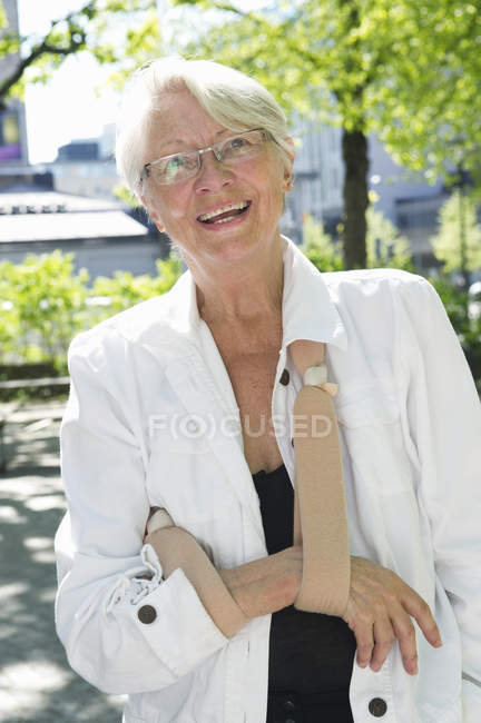 Portrait of senior woman wearing arm sling — Stock Photo