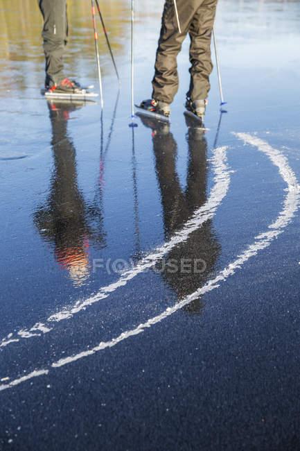 Vue recadrée des hommes mûrs patinant sur le lac gelé — Photo de stock