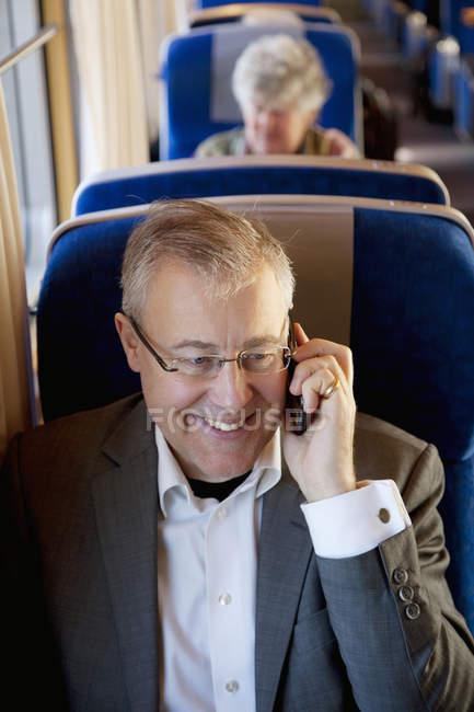 Бизнесмен, говорить на смарт-телефон на поезд — стоковое фото