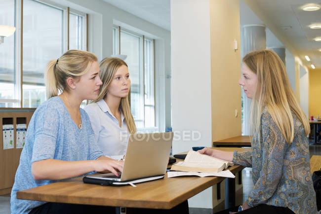 Giovani donne per mezzo del computer portatile mentre studiava all'Università — Foto stock