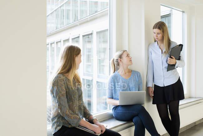 Jóvenes usando laptop y hablando en la Universidad de - foto de stock