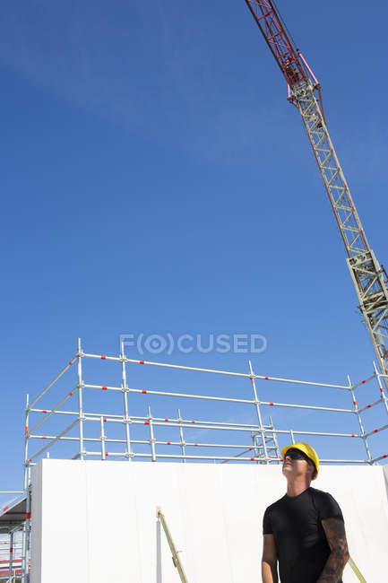 Строительный рабочий, стоя на строительной площадке и глядя вверх — стоковое фото