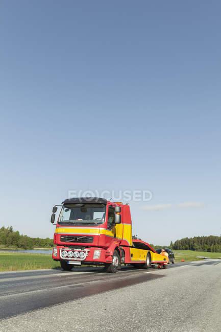Людина, Скрадливий між буксирування вантажівки — стокове фото