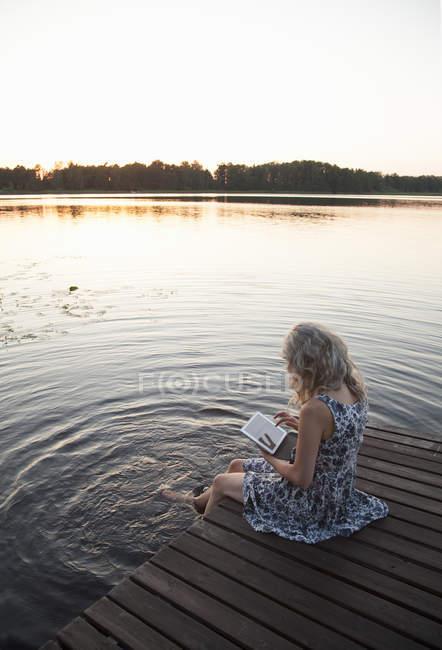 Женщина сидит на причале и использует цифровой планшет — стоковое фото