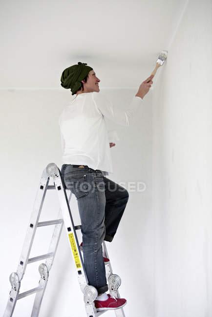 Жінка, стоячи на крок сходи і стіна живопис — стокове фото