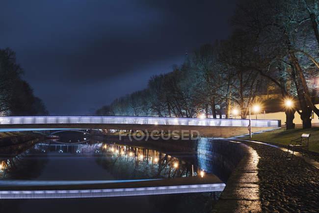 Illuminated bridge over river at night, northern europe — Stock Photo