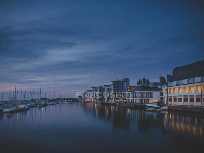 Beleuchtete Häuser durch Kanal in der Abenddämmerung, Nordeuropa — Stockfoto