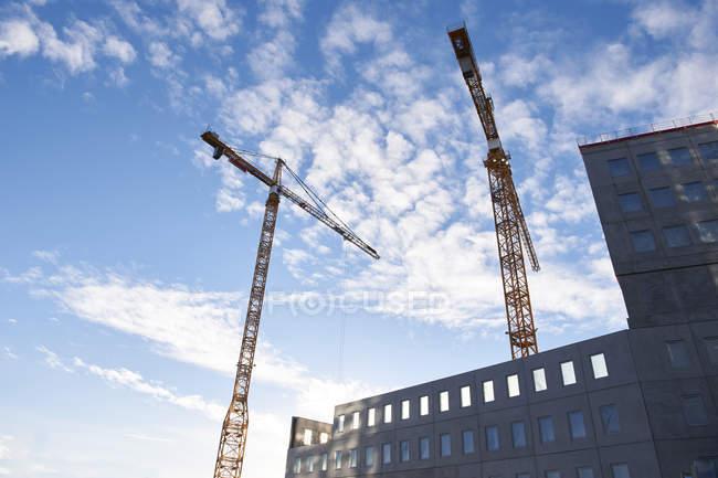 Vue d'angle faible des grues industrielles dans la ville — Photo de stock