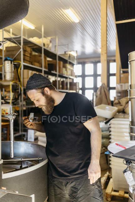 Uomo che controlla i chicchi di caffè, concentrarsi sul primo piano — Foto stock