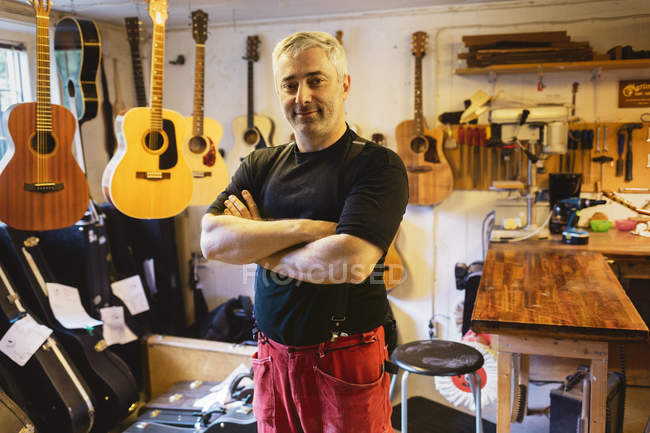 Portrait of craftsman in guitar making workshop, selective focus — Stock Photo