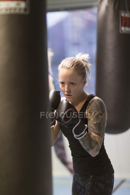 Young woman punching boxing bag in gym, selective focus — Stockfoto