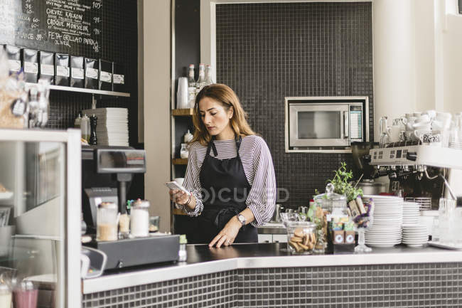 Barista using smart phone at cafe counter, selective focus — Stock Photo