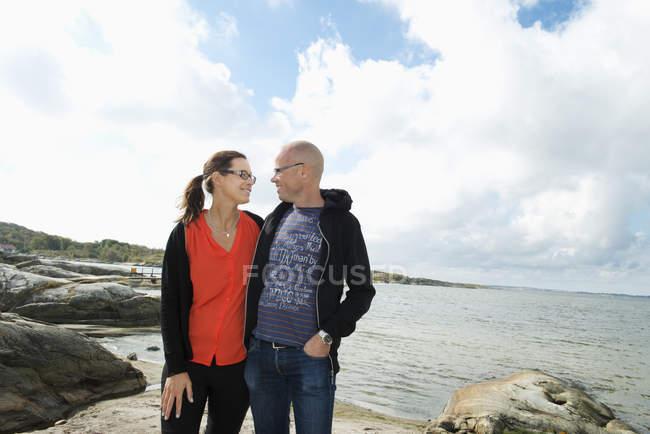 Esposo y esposa de pie en la playa y mirándose el uno al otro - foto de stock