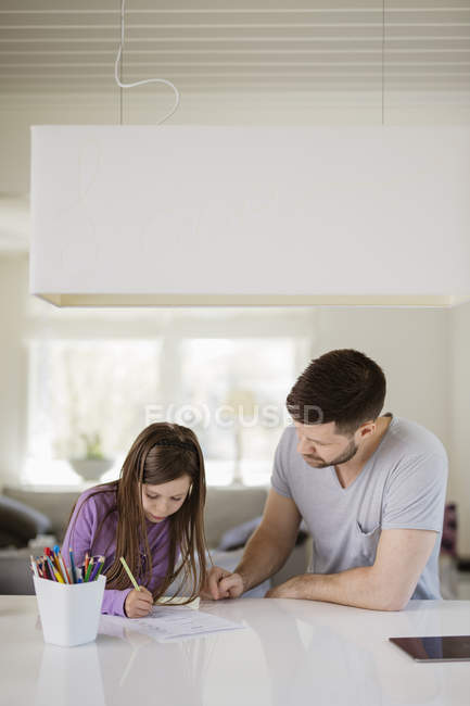 Father and daughter drawing at kitchen, focus on foreground — Stock Photo