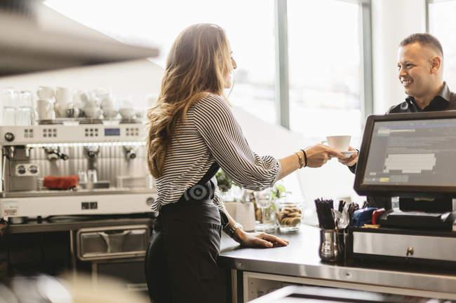 Бариста с чашкой кофе для клиента в кафе — стоковое фото