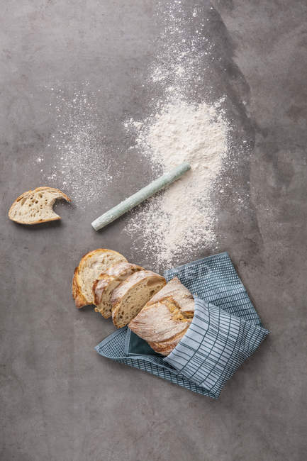 Loaf of bread and flour on grey background — Stock Photo