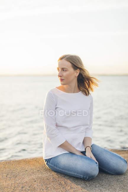 Giovane donna seduta vicino al mare a Karlskrona, Svezia — Foto stock