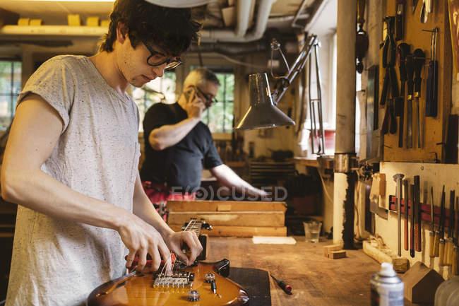 Ремесленник, работающий в мастерской по изготовлению гитары — стоковое фото