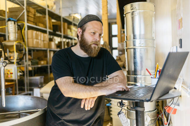Coffee roaster using laptop, focus on foreground — Stock Photo