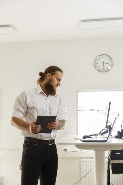 Young businessman looking at laptop, focus on foreground — Stock Photo