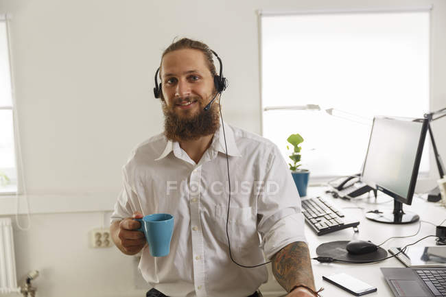 Young businessman with cup and headset, selective focus — Stock Photo