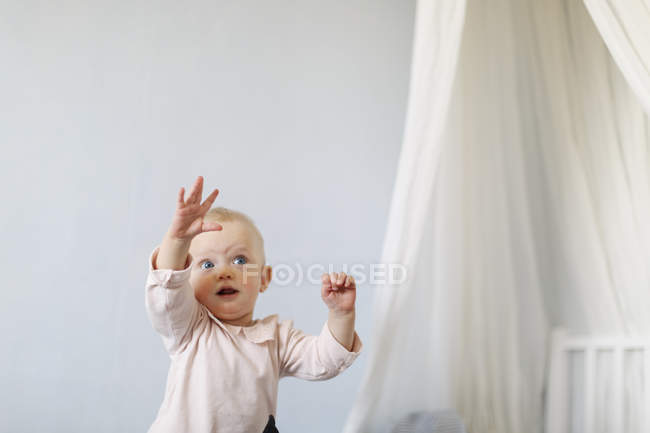 Baby girl reaching up, focus on foreground — Stock Photo