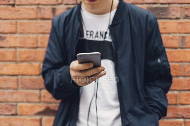 Cropped view of teenage boy listening music on smartphone, selective focus — Stock Photo