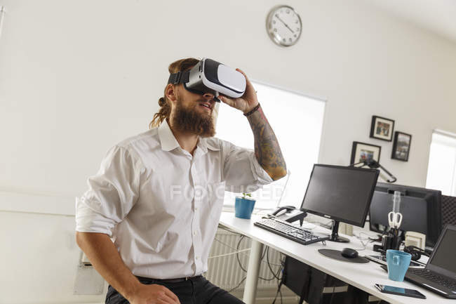 Young businessman wearing virtual reality goggles, selective focus — Stock Photo