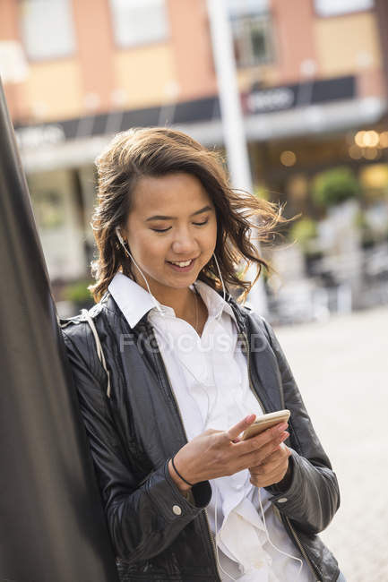 Young woman using cell phone, focus on foreground — Stock Photo