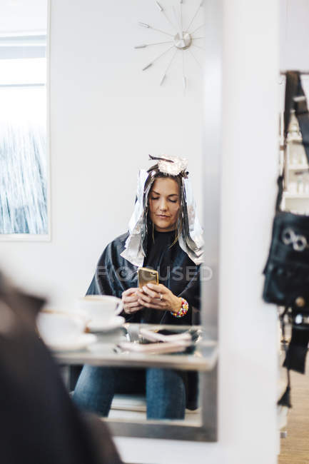 Hairdressing client with foil in hair, selective focus — Stock Photo