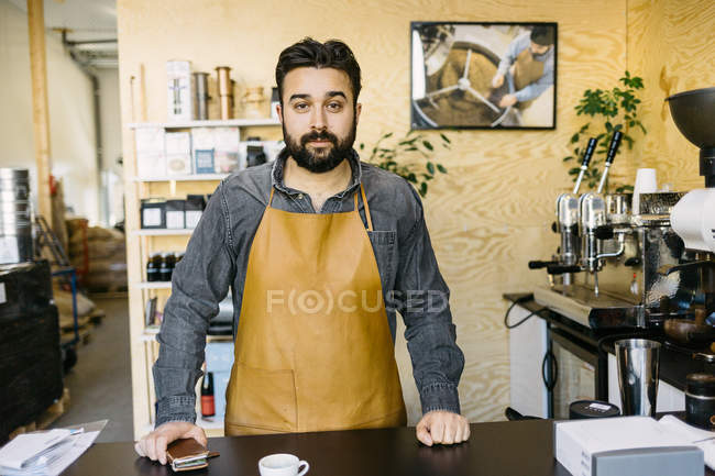 Small business owner looking at camera at coffee roaster shop — Stock Photo