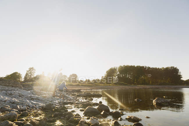 Mother with daughter on riverbank in Gotland, Sweden, lens flare — Stock Photo