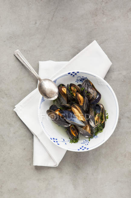 Mussels in bowl with spoon and napkin on grey background — Stock Photo