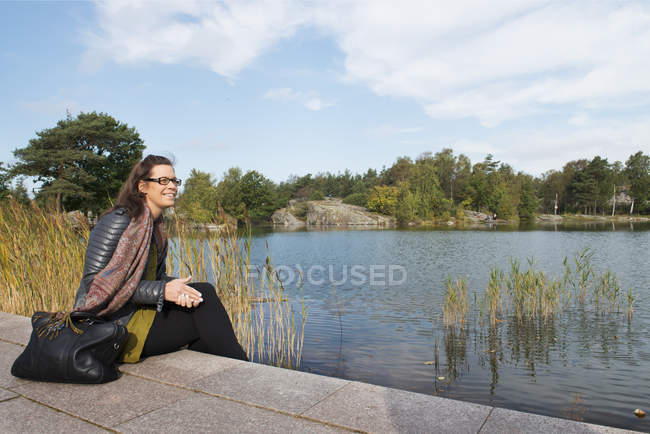 Взрослая женщина, сидящая у озера, избирательный фокус — стоковое фото