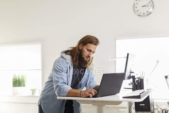 Young businessman using laptop at office, focus on foreground — Stock Photo