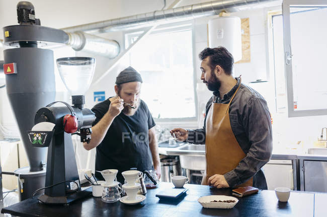 Two men testing coffee at commercial kitchen, selective focus — Stock Photo