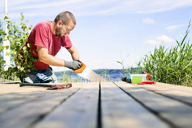 Mid adult man sawing deck, selective focus — стоковое фото
