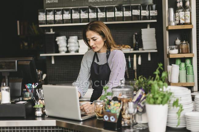 Barista che utilizza computer portatile al bancone del bar, fuoco selettivo — Foto stock