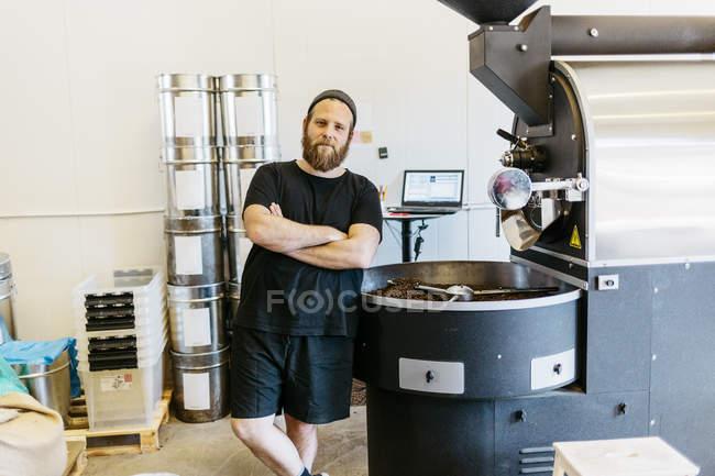 Hombre posando junto a la máquina de asar café - foto de stock