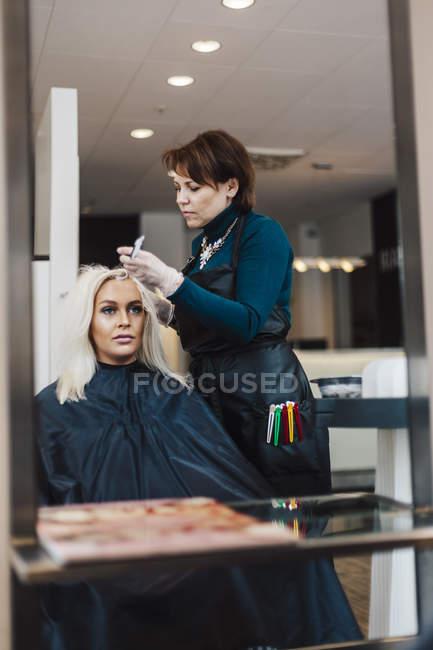 Cabeleireiro coloração do cabelo do cliente, foco seletivo — Fotografia de Stock