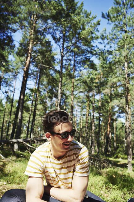 Молодой человек сидит в лесу, фокусируется на переднем плане — стоковое фото