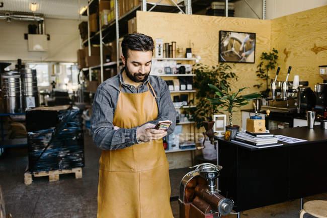 Piccolo imprenditore presso negozio di torrefazione caffè usando smartphone — Foto stock