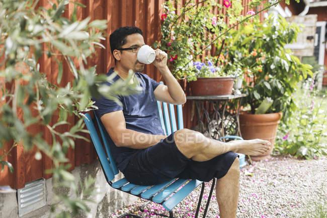 Mann trinkt Kaffee draußen in Mortfors, Schweden — Stockfoto