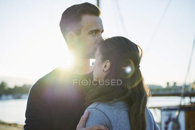 Jeune homme embrasser femme à l'extérieur, se concentrer sur le premier plan — Photo de stock