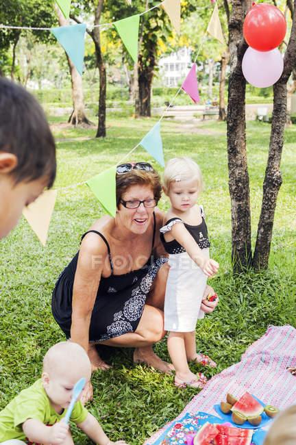 Großmutter mit Enkelkindern beim Geburtstagspicknick — Stockfoto