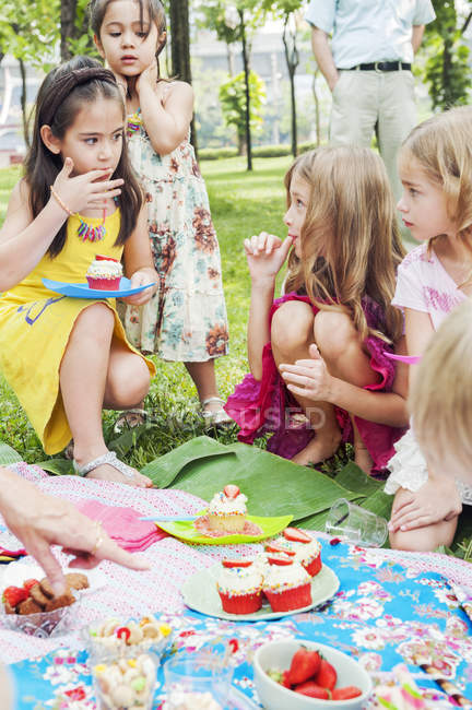 Children having fun at birthday picnic, focus on foreground — стокове фото